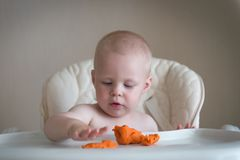 Children creativity. the baby is trying to sculpt from clay. Cute little boy mould from plasticine on table stock image