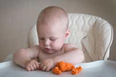 Children creativity. the baby is trying to sculpt from clay. Cute little boy mould from plasticine on table stock photos