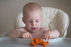 Children creativity. the baby is trying to sculpt from clay. Cute little boy mould from plasticine on table stock photography