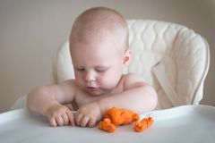 Children creativity. the baby is trying to sculpt from clay. Cute little boy mould from plasticine on table stock photo