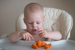 Children creativity. the baby is trying to sculpt from clay. Cute little boy mould from plasticine on table royalty free stock photos