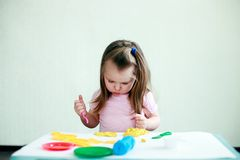 Children creativity. Kid sculpts from clay. Cute little 2 years girl moulds from plasticine on table in room royalty free stock photo