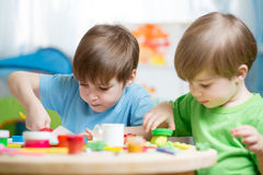 Children creativity. Kids sculpting from clay. Cute little boys mould from plasticine on table in nursery room Royalty Free Stock Photography