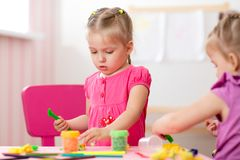 Children creativity. Kids sculpts from clay. Cute little girl moulds from plasticine on table in nursery Stock Image