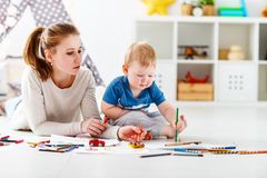 Children creativity. mother and baby son drawing together Stock Photos
