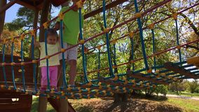 Children cross bridge on playground. Two clips of children cross suspension rope bridge on playground at summer sunny day. Big brother teenager supports little stock video footage