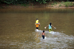 Children cross a stream Royalty Free Stock Images