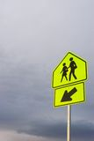 Children crossing. A bright fluorescent caution sign on a pole Royalty Free Stock Photos