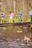 Children Crossing Bridge As Dog Plays In Stream Royalty Free Stock Photography