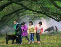 Children crossing farm field, China countryside