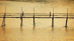 Children crossing the river on a bamboo bridge. Luang Prabang, Laos stock video footage