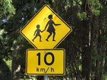 Children crossing road sign. An Australian road sign for being aware of children crossing the street - with a recommended speed limit of 10 km/h Royalty Free Stock Images