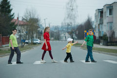 Children crossing street on crosswalk Stock Photos