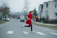 Children crossing street on crosswalk. Photo of girl crossing street on the crosswalk Stock Images