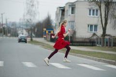 Children crossing street on crosswalk. Photo of girl crossing street on the crosswalk Stock Photography