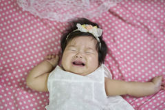 The children crying on the bed. Baby girl Asian, the children crying on the bed Royalty Free Stock Images