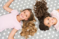 Children curly hairstyle relaxing. Keep hair curly even next morning. Girls children with long hair lay on bed top view. Conditioner mask organic oil keep hair stock photography
