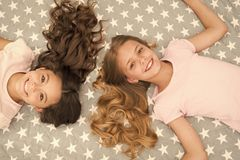Children curly hairstyle relaxing. Keep hair curly even next morning. Girls children with long hair lay on bed top view. Conditioner mask organic oil keep hair royalty free stock images