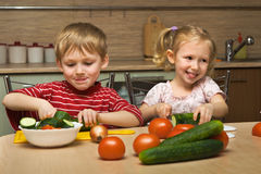 Children cut vegetables Royalty Free Stock Photography