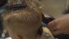 Children cutting concept. Hairdresser cutting hair little boy with electrical razor in barber salon. Kids haircut with. Hair machine close up. Barber doing stock video footage