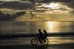 Children cycling on the beach on sunset, Thailand Royalty Free Stock Photography