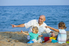 Children with Dad on beach royalty free stock photos