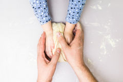 Children and dad hands make a dough. Top view children and dad hands make a dough on the wooden table stock image