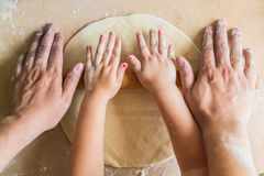Children and dad hands rolled dough. With a rolling pin on the table Stock Photo
