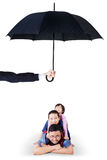Children and dad lying in studio under umbrella Stock Image
