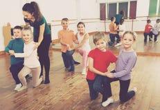 Children dancing tango. Group of positive children  8-9 years old dancing tango in dance studio Stock Image