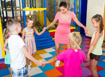 Children dancing with teacher to music in class at school. Excited european children dancing with teacher to music in class at school Stock Image