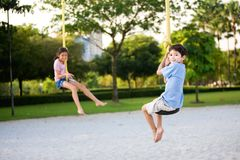 Children dangling on the suspension rope in playgr Stock Images