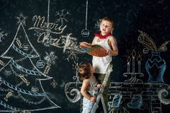 Children decorate the Christmas tree. Brother and sister draw a Christmas song on the wall .Merry Christmas Stock Images