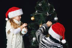 Children decorate the Christmas tree in the room. Merry Christmas and happy holidays royalty free stock photo