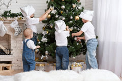 Children decorate a Christmas tree toys. Four young children decorate the Christmas tree with beautiful toys royalty free stock image