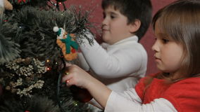 Children decorate the christmas tree. Two caucasian children decorating the christmas tree. Little boy and girl preparing for the Christmas together. Little kids stock video footage