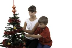 Children decorate a New Year tree Royalty Free Stock Images