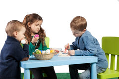 Children decorating Easter eggs. Three young children decorating Easter eggs sit around a table with a basket of colourful painted eggs between them while a Royalty Free Stock Photography