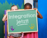 Children demanding on chalkboard. Two children demanding on chalkboard in German Integration jetzt! (Integration now Royalty Free Stock Images
