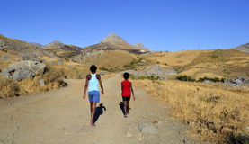 Children in desert area. Children walking in a desert area The picture was taken on the island of Crete, Greece stock photo