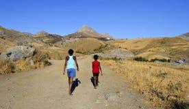 Children in desert area. Children walking in a desert area The picture was taken on the island of Crete, Greece Stock Photo