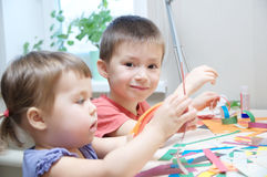 Children development - brother and sister making paper garland Stock Photography