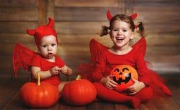 Children are devil costume with pumpkins prepared for Halloween Stock Photo