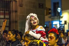 Children at Dia de Muertos Parade. A young girl in costume rides atop her father`s shoulders at a Day of the Dead parade in Oaxaca, Mexico Stock Photos