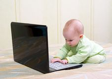 Children in diapers playing with a laptop computer Stock Image