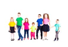 Children of different ages isolated. Children of different ages are standin and holging hands, wearing in rainbow t-shirts, isolated on white royalty free stock images