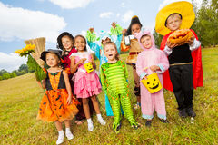 Children in different Halloween costumes standing Royalty Free Stock Images