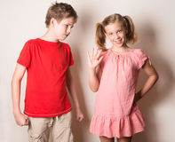Children in different moods. Sister teasing her brother, fake sm