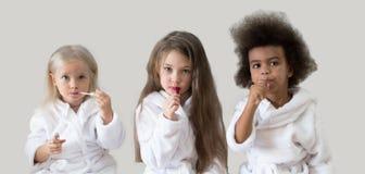 Three girls girlfriends apply lipstick stock photography