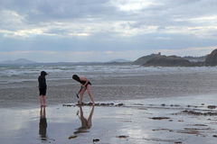 Children digging on a cloudy Welsh beach. Stock Image